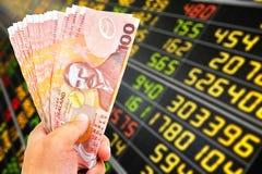 New zealand doller bill. Man`s hand holding new zealand doller bill on stock market background Royalty Free Stock Photo