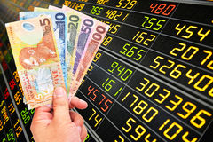 New zealand doller bill. Man`s hand holding new zealand doller bill on stock market background Royalty Free Stock Images