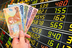 New zealand doller bill on stock market background. Man`s hand holding new zealand doller bill on stock market background Stock Images