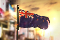New Zealand Flag Against City Blurred Background At Sunrise Back stock image