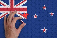 New Zealand flag is depicted on a puzzle, which the man`s hand completes to fold.  royalty free illustration