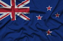 New Zealand flag is depicted on a sports cloth fabric with many folds. Sport team banner. New Zealand flag is depicted on a sports cloth fabric with many folds royalty free stock image