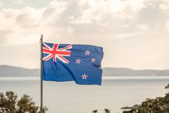 New Zealand Flag. With the ocean in the background Stock Images