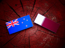 New Zealand flag with Qatari flag on a tree stump isolated. New Zealand flag with Qatari flag on a tree stump Royalty Free Stock Image