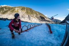 Tour guide awaits for a helicopter at fox glacier, New Zealand. NEW ZEALAND, FOX GLACIER - MAY 2016: An unidentified tour guide awaits for a helicopter bringing stock photos
