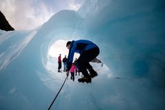 Tourist hikes through a hole at fox glacier, New Zealand. This glacier is one royalty free stock photo