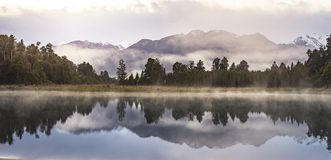 New Zealand lake view refection with morning sunrise sky. New Zealand lake view, pine forest reflected on lake with morning sunrise sky Royalty Free Stock Photography