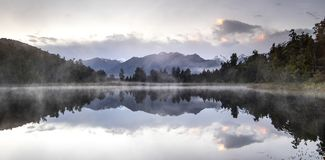 New Zealand lake view refection with morning sunrise sky. New Zealand lake view, pine forest reflected on lake with morning sunrise sky Stock Image