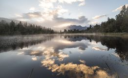 New Zealand lake view refection with morning sunrise sky. New Zealand lake view, pine forest reflected on lake with morning sunrise sky stock photo