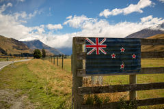New Zealand landscape. NZ flag on fence Royalty Free Stock Photo