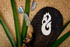New Zealand - Maori themed objects - carved mere and bone pendan. New Zealand - Maori themed objects - carved wooden mere and bone pendant on woven kite flax Royalty Free Stock Images