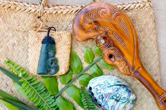 New Zealand - Maori themed objects - Jade Pounamu pendant, Paua. Shell, Wooden Patu with Kite bag, fern and flax leaves on woven background stock photos