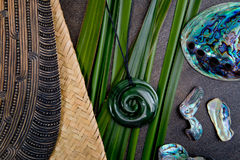 New Zealand - Maori themed objects - mere and greenstone pendant. New Zealand - Maori themed objects - carved wooden mere and greenstone pendant with green flax stock image
