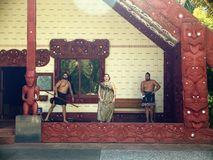 New Zealand: native Maori cultural performance. Maori woman and two men singing and performing outside meeting house marae royalty free stock photo