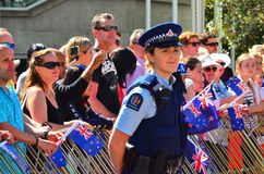 New Zealand police officer woman guarding crowd of people Royalty Free Stock Photos