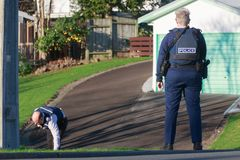 New Zealand police. A policewoman watches while a colleague searches. A female member of the New Zealand police force stands guard with a holstered Glock pistol stock photo