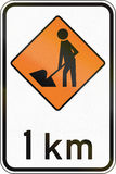 New Zealand road sign - Road workers ahead in 1 kilometre Stock Image
