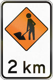 New Zealand road sign - Road workers ahead in 2 kilometres Stock Photo