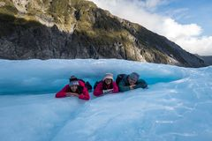 Group of travellers laying under a ice arch at Fox Glacier in New Zealand royalty free stock image