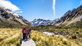 NEW ZEALAND, SOUTH ISLAND, MOUNT COOK - FEBRUARY 2016: A group of young traveler explores Valley track. Working holiday. Visa is popular among young people and royalty free stock image