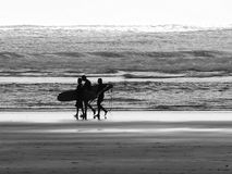 New Zealand surfers. Surfers walk down a desolate beach in New Zealand Royalty Free Stock Photo