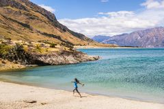 Free New Zealand Travel Happy Tourist Woman Running Of Joy And Freedom At Beach Shore Of Lake Hawea Nature Landscape. Near Wanaka, Royalty Free Stock Photography - 156683107