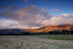 New Zealands mountains covered in clouds at sunset Stock Photos