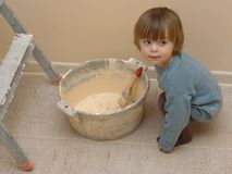 Newbie in flat renovation. Little boy near the bucket with paintbrush on the background of fresh paint Stock Images