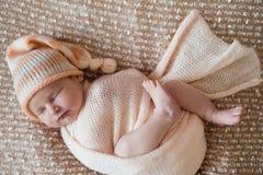 Newborn девушка, сладостно уснувшая в пеленке, нося розовую оранжевую крышку стоковое фото rf