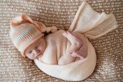 Newborn девушка, сладостно уснувшая в пеленке, нося розовую оранжевую крышку стоковые фотографии rf