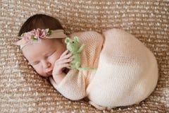 Newborn девушка, сладостно уснувшая в пеленке, нося розовую оранжевую крышку стоковое изображение