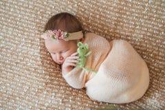 Newborn девушка, сладостно уснувшая в пеленке, нося розовую оранжевую крышку стоковая фотография rf