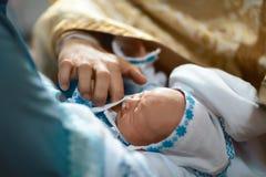 Newborn крещение младенца маслом с руками священника стоковое фото rf