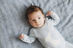 Newborn милый ребенок в голубом sleepwear лежа на сером листе, взгляде сверху стоковое фото