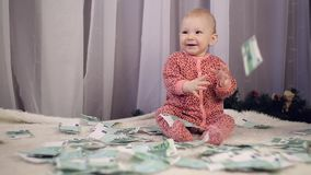 Newborn младенец выглядит как деньги падает на его сток-видео