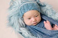 Newborn младенец лежа в ринве с голубым одеялом стоковые изображения rf