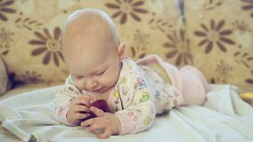 Newborn младенец лежа на кровати и есть Яблоко сток-видео