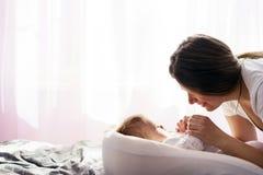 Newborn младенец лежит на кровати и мать держит его руки стоковая фотография rf