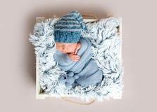 Newborn младенец спать в коробке среди голубых одеял Стоковая Фотография RF