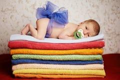 Newborn младенец лежа на красочных полотенцах Стоковая Фотография RF
