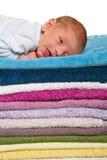 Newborn младенец лежа на красочных полотенцах Стоковые Изображения RF