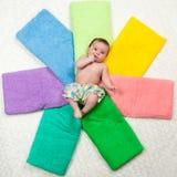 Newborn младенец лежит на пестротканых полотенцах Счастье Стоковые Фото