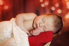 Newborn младенец на красной предпосылке Стоковые Изображения