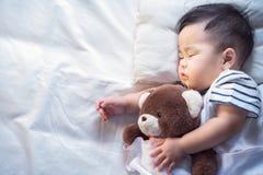 Newborn сон младенца с плюшевым медвежонком Стоковая Фотография