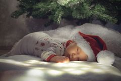 Newborn сон ребёнка под рождественской елкой на белой земле освещения Стоковые Изображения RF