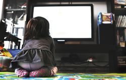 Newborn ТВ вахты младенца на ковре в гостиной socks задний взгляд стоковое изображение