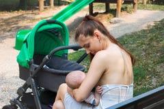 Новая мама с ее newborn снаружи, задний взгляд со стороны младенца молодой матери кормя грудью публично, стоп пока идущ с pram стоковые фотографии rf