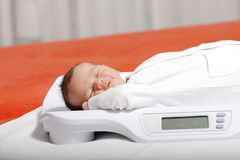 Newborn. Baby boy on weight scale Royalty Free Stock Photography