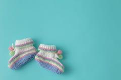 Newborn announcement. knitted baby booties on plain aquamarine b Stock Photos