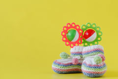 Newborn announcement. knitted baby booties on plain yellow backg Stock Images
